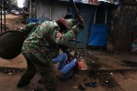 A resident of the Mathare slum of Nairobi gets beat by Kenyan police during clashes in the slum city.