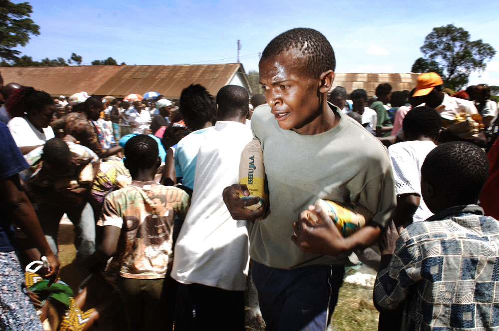 A man caries bags of flour during a food distribution at the Kibera slums after a bitter week of violence in Nairobi.