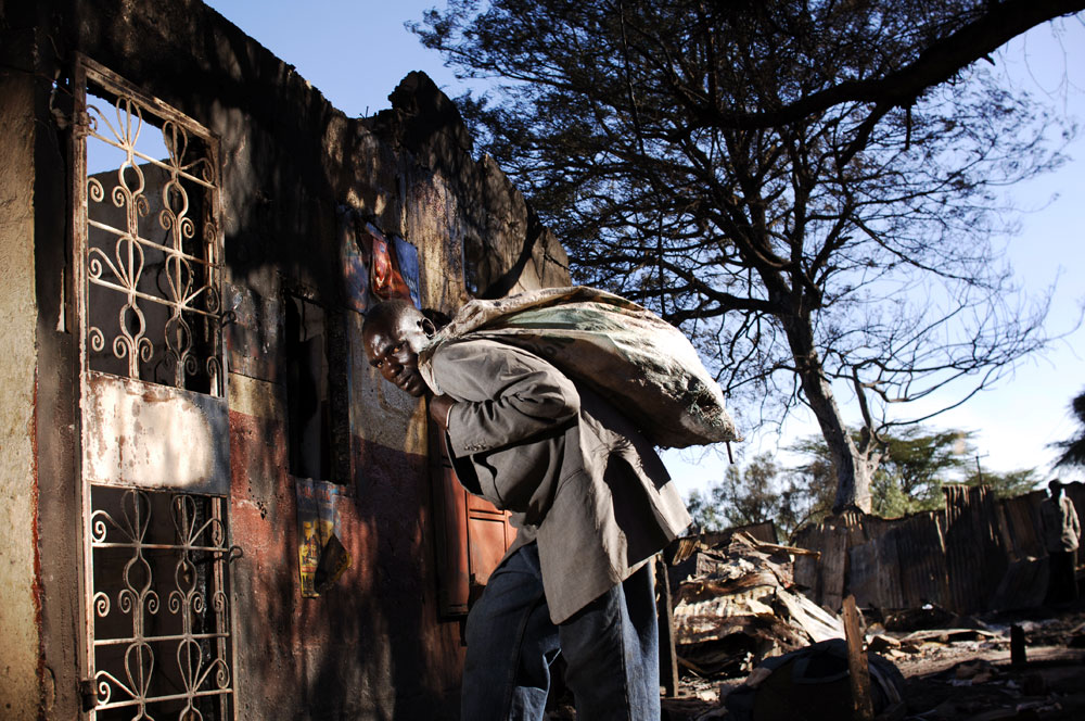 A man looks for goods near a building that has been looted and burned in Kibera slum in Nairobi.