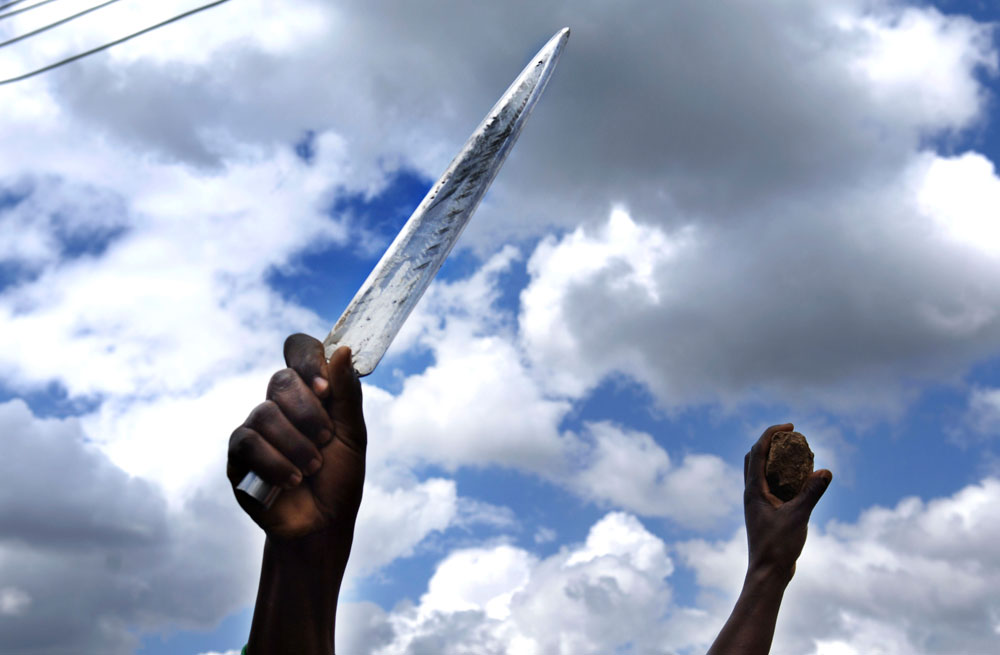 Resident of the Mathare slum of Nairobi show off a knife as they clash with Kenyan police in violence sparked fallowing the December elections.