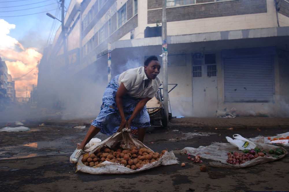 A woman selling vegetables folds her good after riot police shot tear gas in down town Nairobi as supporters of Kenya's Opposition leader Raila Odinga took to the street causing down town Nairobi to  become a seen of clashes and mayhem.