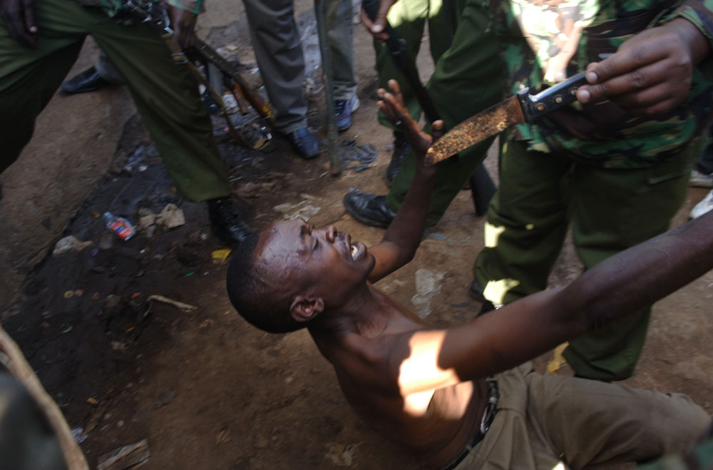 A Kenyan man lays on the ground, surrounded by riot police, after the have found a knife on him.