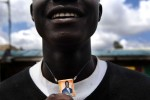 A resident of the Mathare slum of Nairobi shows a necklace of Rila Odinga during clashes with Kenyan police.