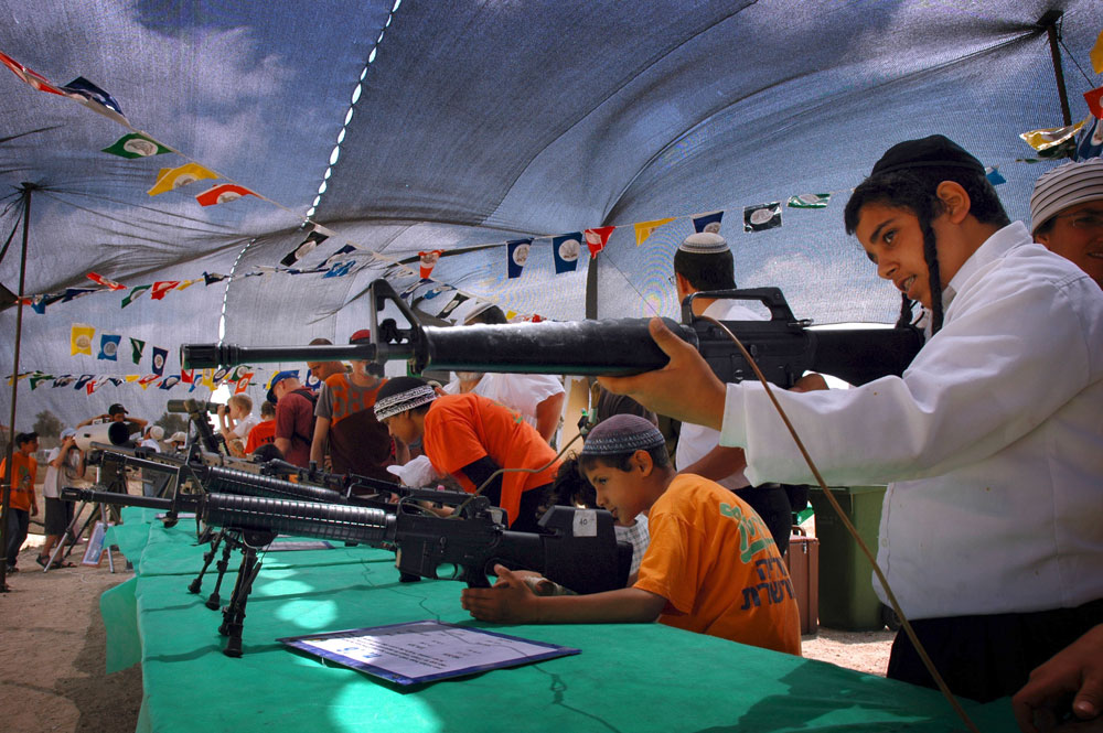 A Jewish boy aims a rifle at the Israeli army military equipment exhibition on Israeli Independence Day in Gush Katif settlement block, Gaza.