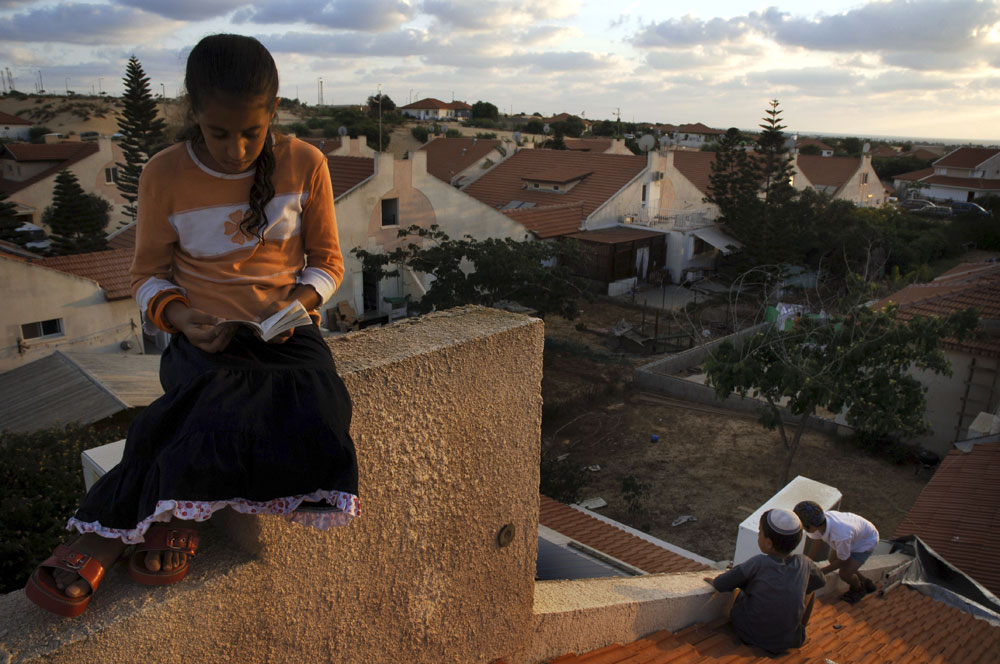 A Jewish settler girl sits on a roof during a mass prayer aimed against the disengagement plan in Gush Katif settlement block, Gaza.