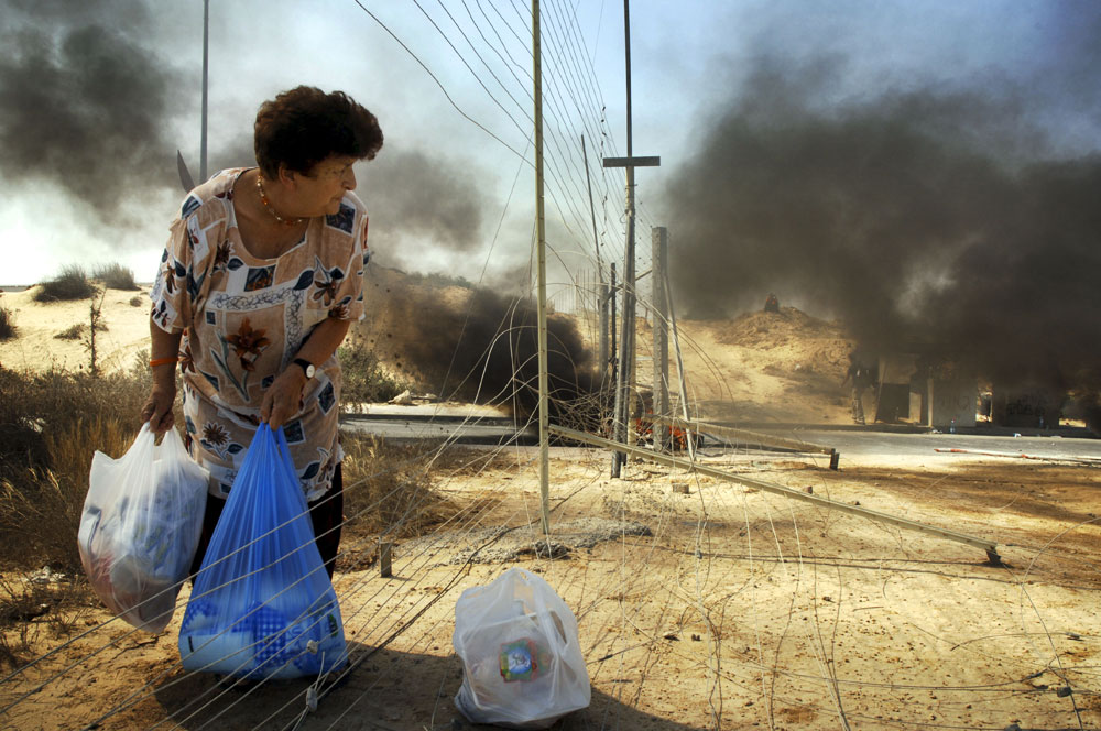 An Israeli settler woman takes her shopping bags throe the fence as tires burn in the back round during the pullout operation in Neve Dekalim, Gush Katif settlement bloc, Gaza