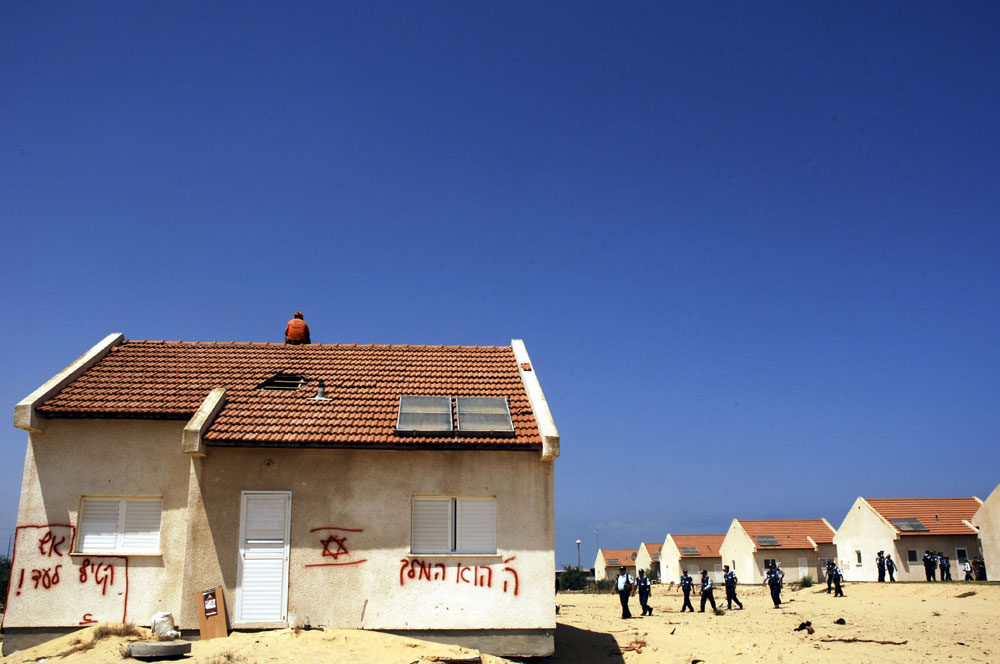 Israeli police walk up to a house with a teenage settler on the roof as he rejects been evicted from Gush Katif settlement bloc, Gaza.