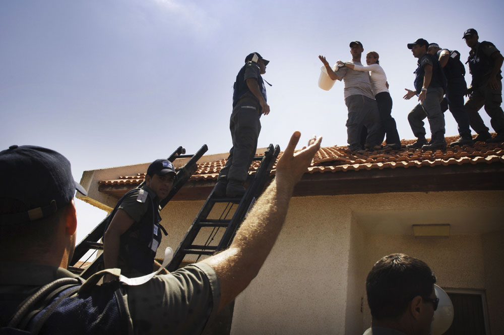 Israeli police climb onto a roof to evict a family from their home in the Jewish settlement of Gadid in Gush Katif settlement bloc, Gaza.