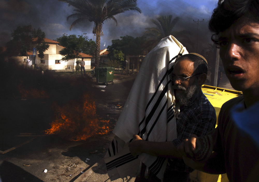 An Israeli settler escapes from a fire with the Torah book during the evacuation of the settlement of Neve-Dekalim in Gush Katif settlement bloc, Gaza.