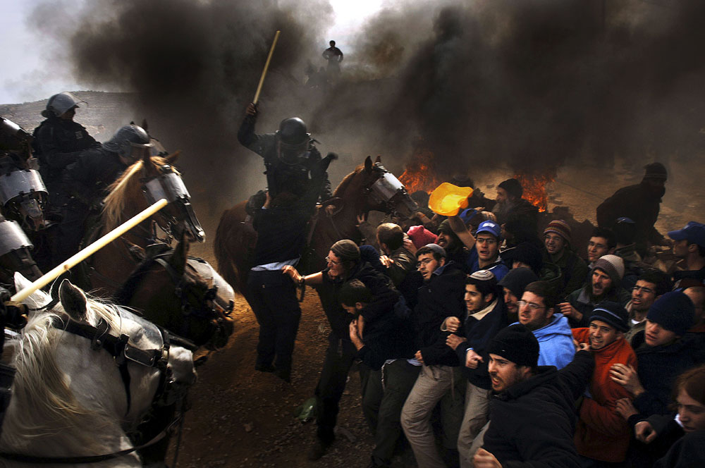 Israeli riot police use horses to clash with Israeli settlers and enter the West Bank outpost of Amona.