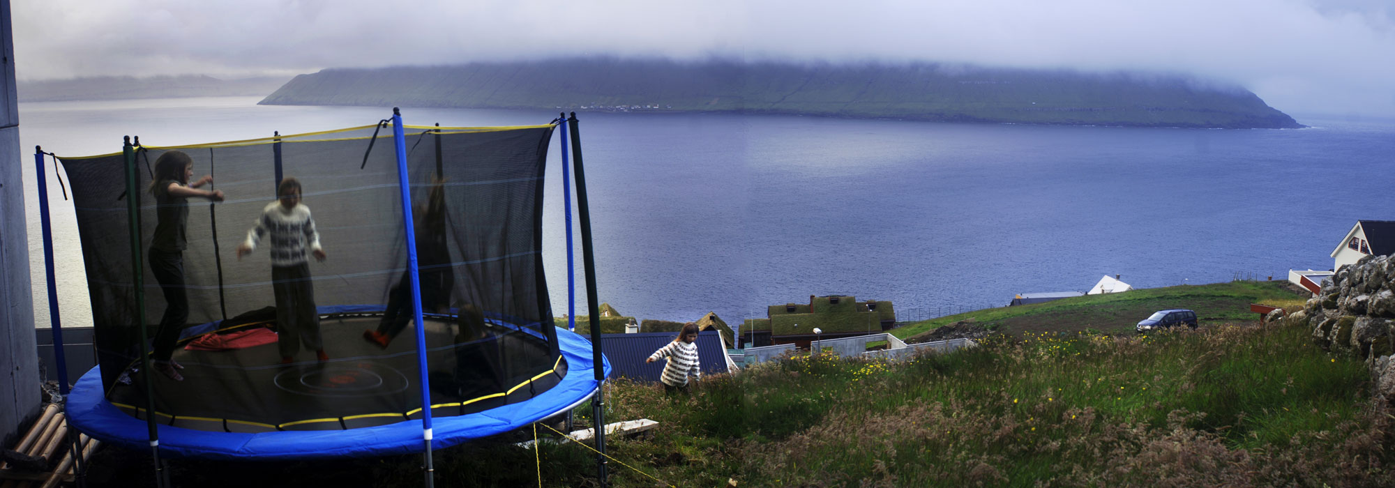 Young girls play in their back yard jumping  on a trampoline in the Southern part of Streymoy Island of the Fare Islands.