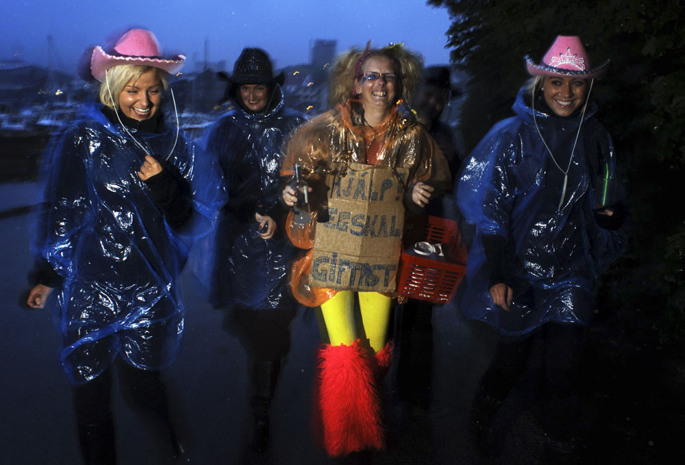 Young women wear plastic rain coats as they make their way to a bar to celebrate  a bachelorette party in Torshavn the capital of the Faore Islands.