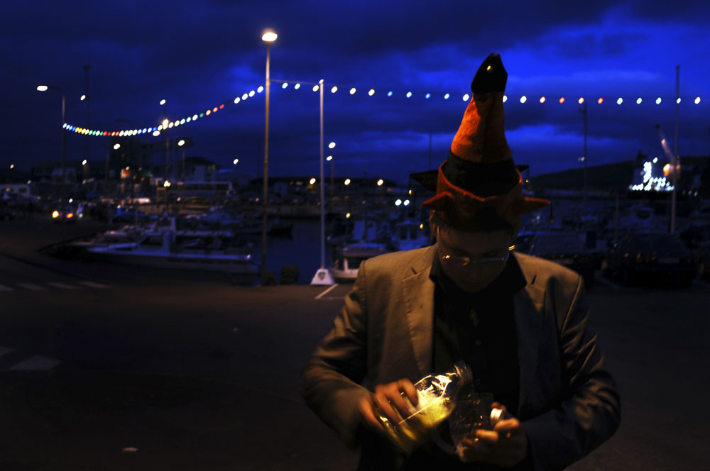 A young man has a drink as night falls on Torshavn during St. Olav's Day - The National Festival in Torshavn the capital of the Faore Islands.