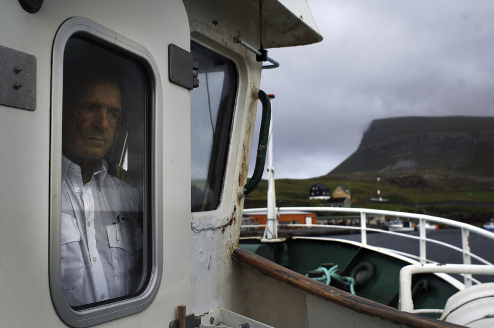 The captain of a small ferry boat connecting between Torshvan and the Island of Nolsoy looks out the window before  heading out to sea. Many of the 18 Islands in the Faroe Islands can be reached only by sea making it hard to get around when the weather dose not permit.