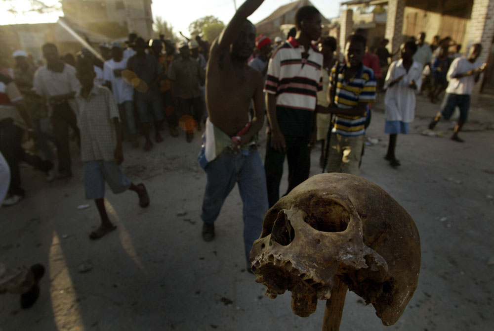 A human skull stands on a stick as Haitian rebels in Gonaives Patrol the streets fallowed by hundreds of supporters.