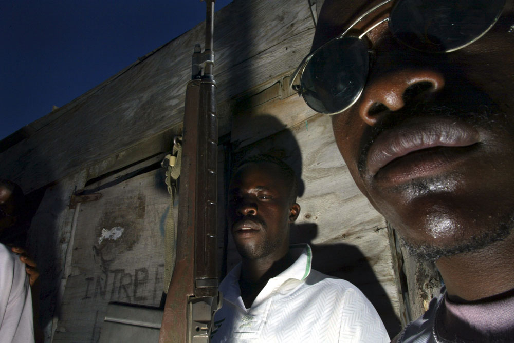 Haitian rebels protect a hut serving as a command center for Buteur Metayer leader of the Gonaives resistance.