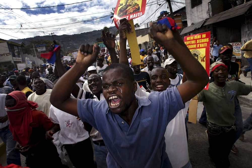 Anti Aristide protesters marche the streets of Port-au-Prince before clashing with police forces.