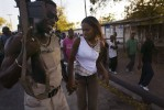 A Haitian rebels and his girl friend in Gonaives Patrol the streets fallowed by hundreds of supporters.