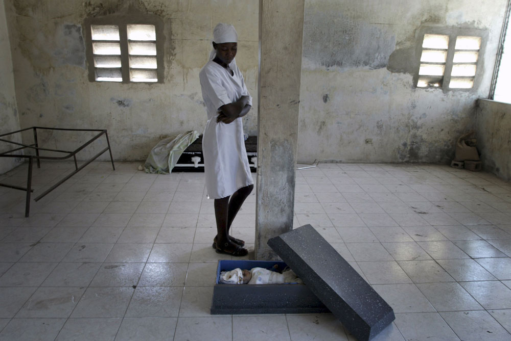 A mother looks over her dead baby in the morgue. The hospital in Gonaives has been closed ever since the rebels took control of town causing many deaths.