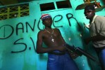 A teenage rebel holds a gun at the entrance to one of the rebel houses in Gonaives.