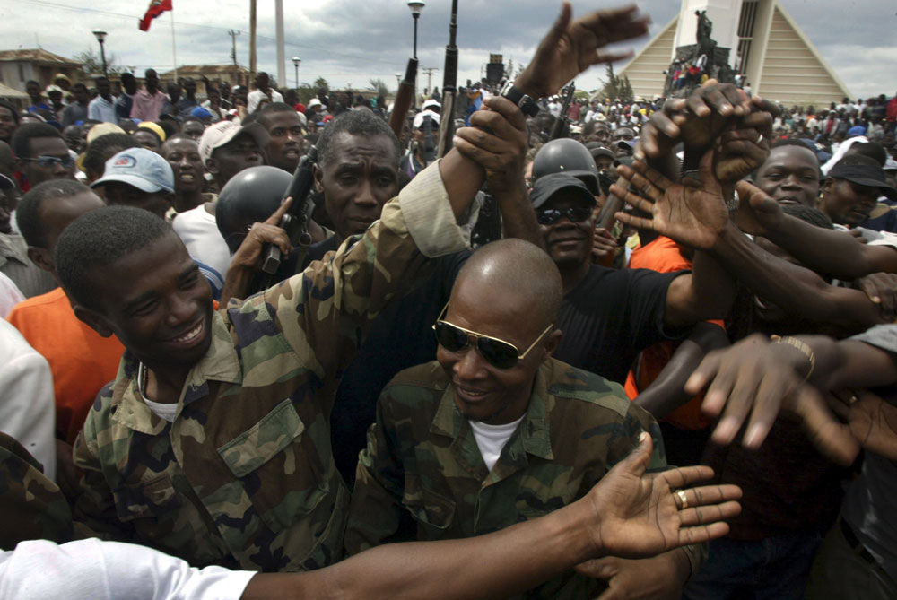 Rebel commander Guy Phillip greets a crowd of thousands at the center square in the city of Gonaives during an anti Aristide march in the rebel controlled city of Gonaives.