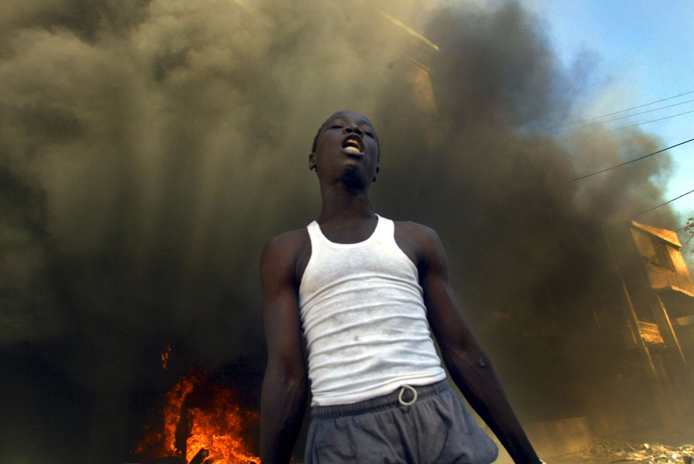 An Aristide supporter stands in front of a building torched by the pro Aristide mob after hearing the news that Prime Minster Aristide resigned and fled the country.
