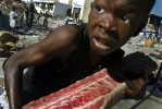 A child runs with a piece of raw meet as mass looting takes place in the Port-au-Prince harbor the day after president Aristide fled the country and lawlessness spread around the capitol.