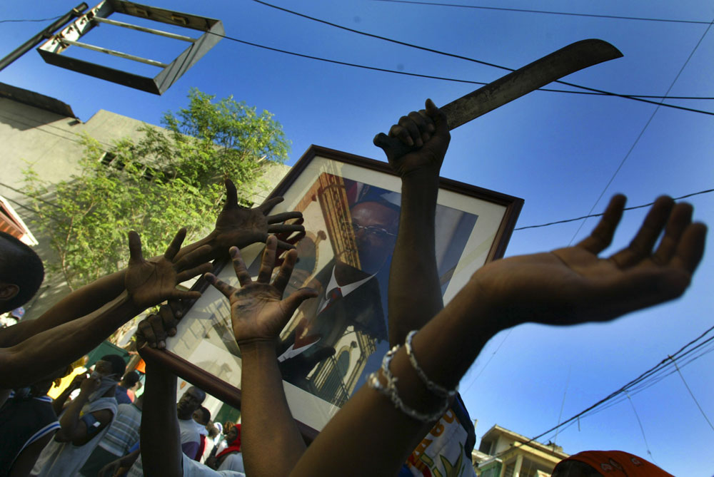 Aristide supporters hold a picture of him in the air as they rally in down town Port-au-Prince the day after president Aristide fled the country and lawlessness spread around the capitol.