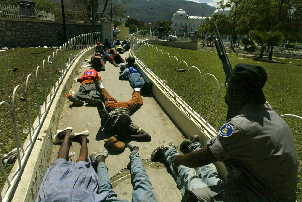 Member of the Haitian National Police kneels as civilians hit the floor when gun fire  spread in front of the white house. The day after president Aristide fled the country lawlessness spread around the capitol.