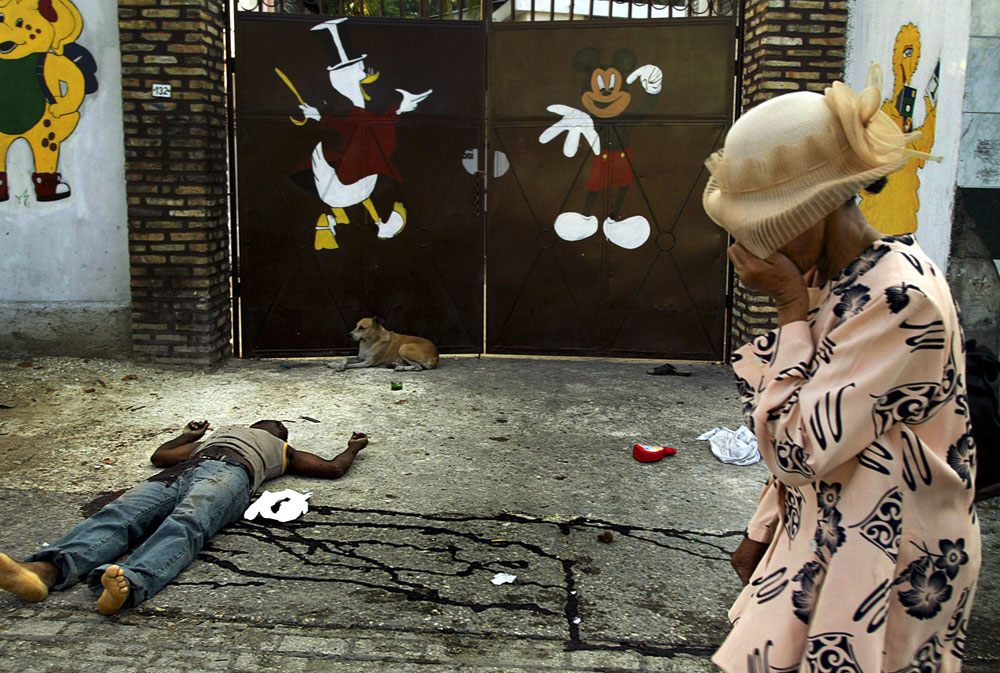 A women walks by a body left on the ground during a bloody shoot-out days after president Aristide fled the country and lawlessness spread around the capitol.