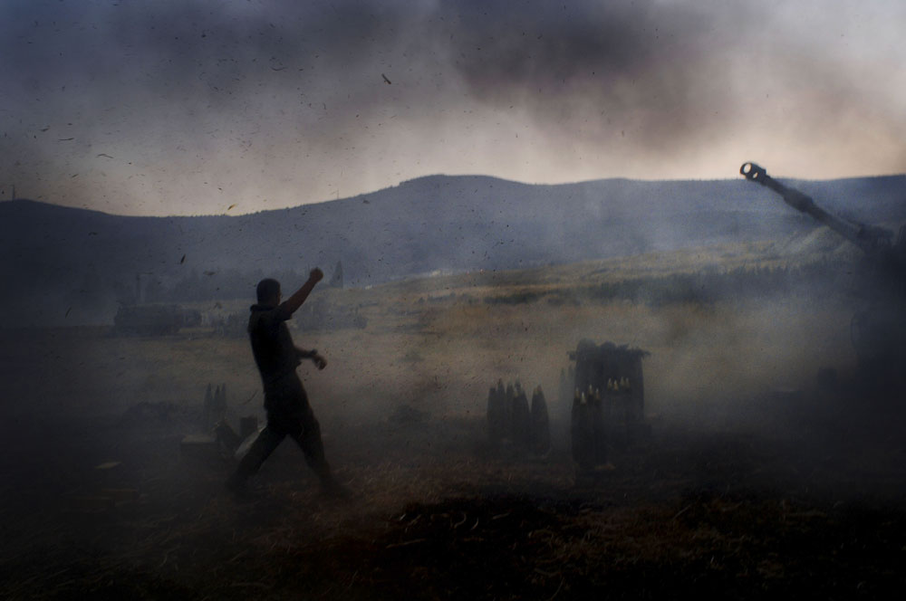 An Israeli soldier reacts as an Israeli mobile artillery unit fires towards Hezbollah targets in southern Lebanon.