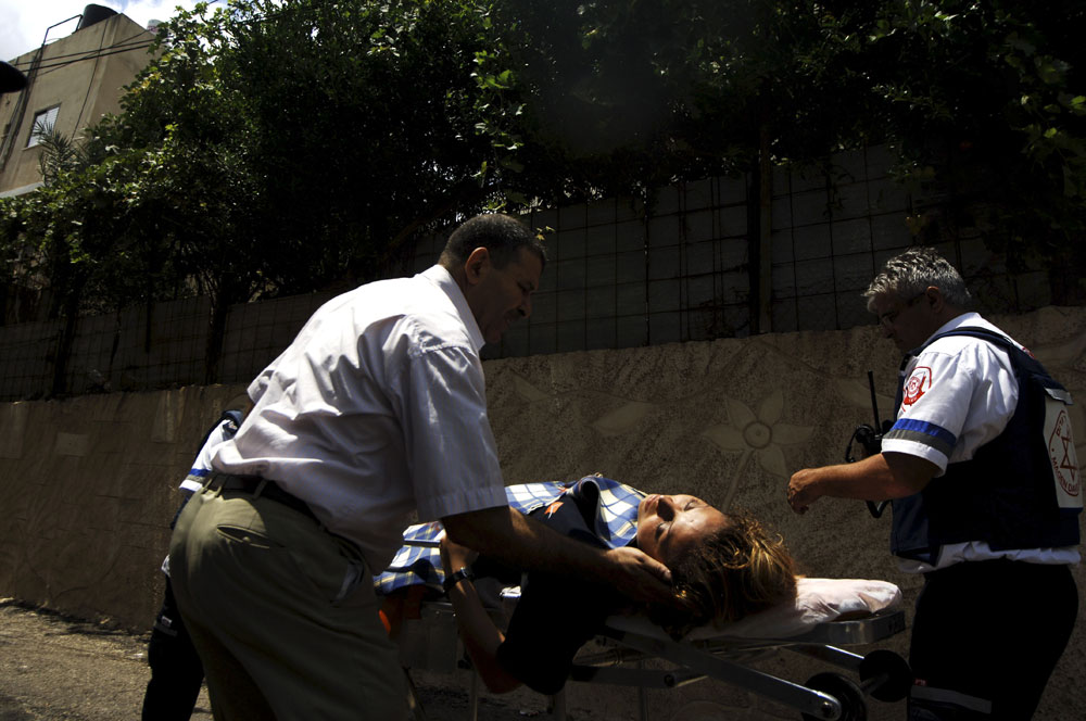 Rescue workers carry an injured woman after a Hezbullah missile attack in the Arab Israeli town of Deir Al-Assad .