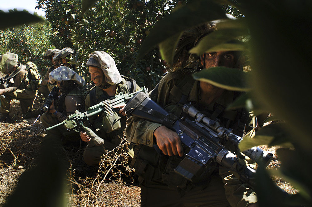Israeli soldiers take positions along the Israeli Lebanese border prior to entering into Lebanon.