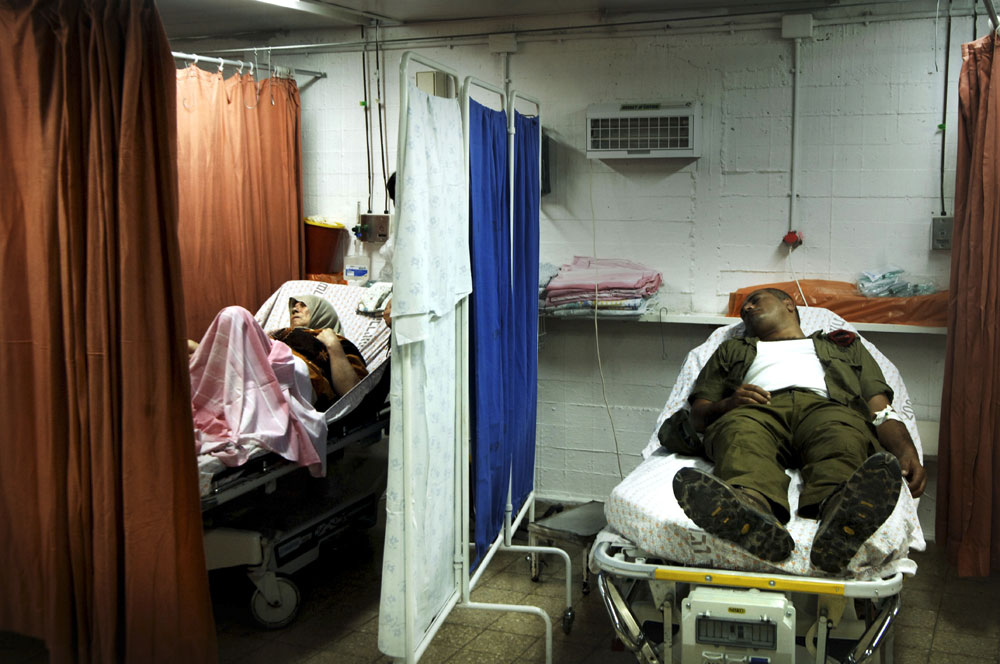 A wounded Israeli soldier is bed to bed with an Israeli Arab lady in the emergency room at the Nahariya Hospital.