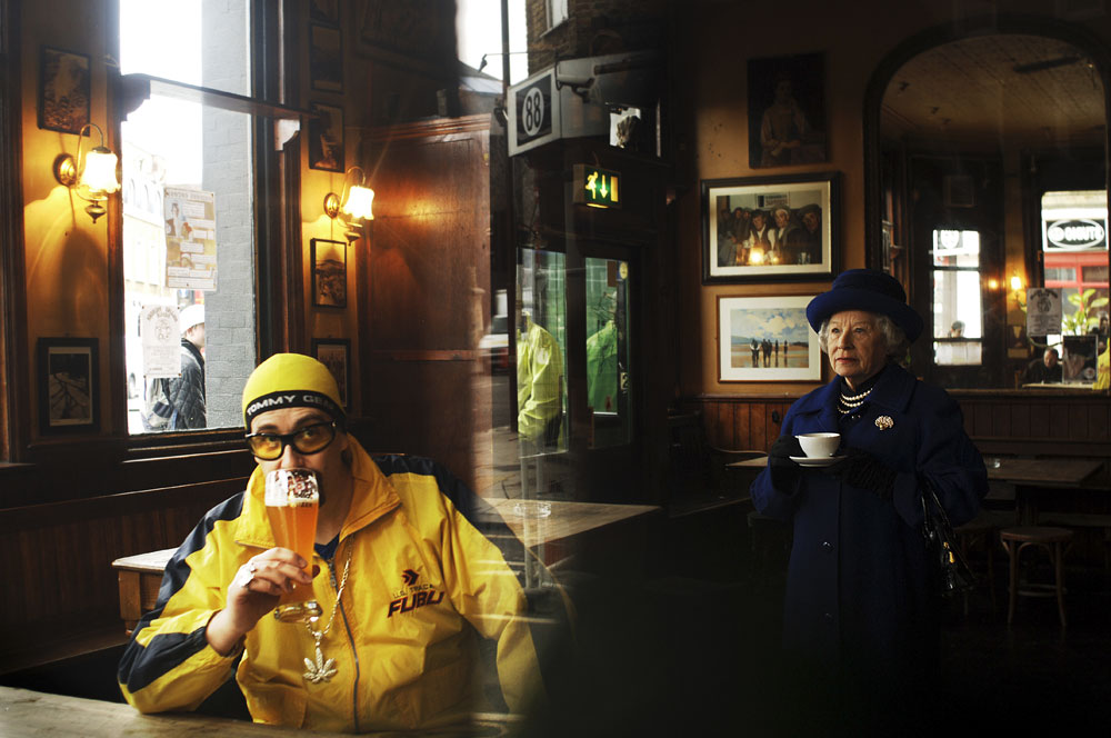Stuart Morrison drinks a beer while impersonating Ali G along side Patricia Ford, a Queen Elizabeth II impersonator in London, England.