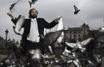 Colin Miller impersonates the famous Opera Singer, Luciano Pavarotti in Trafalgar Square, home to hundreds of pigeons that flock there daily in London, England.