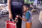 A young boy plays with a barbie doll as he leans on his mother outside his house.