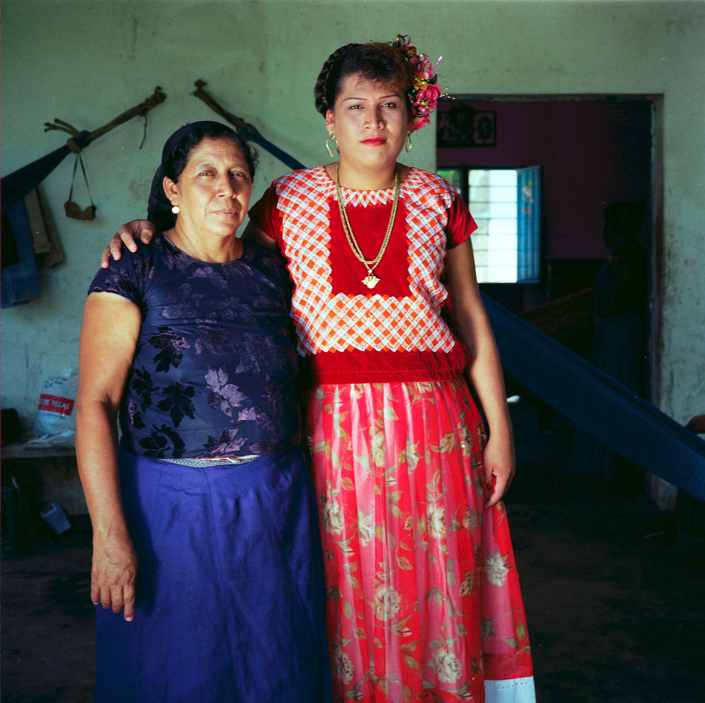 25 years old  Felicza Jimenez Regalado, and  his mom Antonia Regalado Jimenez, 46 proudly pose for a picture  outside their house in Juchitan, Mexico.
