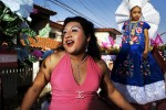 Carla dances on a moving wagon as it parade throe the streets during fiesta in Juchitan, Mexico.