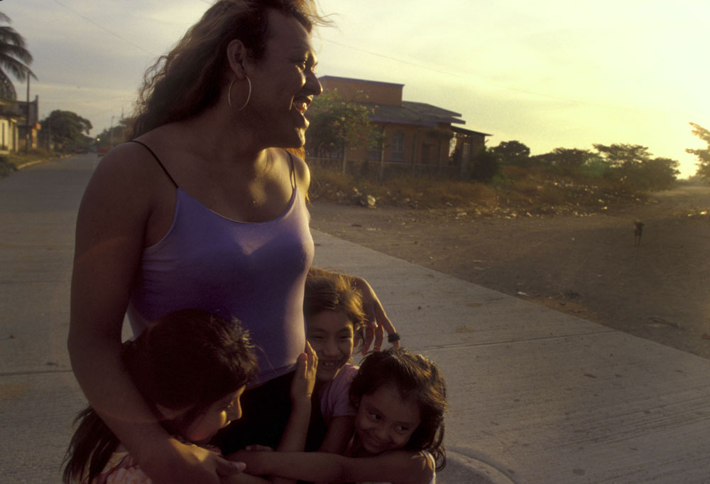 Erica hugs her brother's children as she comes home from work. At the age of 25 she is the sole provider of her family supporting her parents as well as a few children.