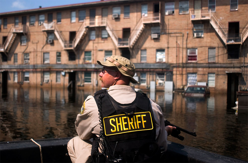Bernalillo County Sheriff's Department Sgt. Paul Jacobs scans building after building of the besieged B.W. Cooper housing project buildings near downtown New Orleans from an air boat. He was searching for people to take out of the flooded area on Sept. 5. His boat floats on a mixture of water, gas, oil, sewage and mud.