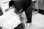 Pepa Robinson Rashad, gently coaxes her youngest daughter into putting medicine on her lips while at the hospital for treatment. For a time, Pepa wore Sponge Bob Square Pants slippers because they made her laugh. As Mooda's treatment stretched into months she wore out the slippers.
