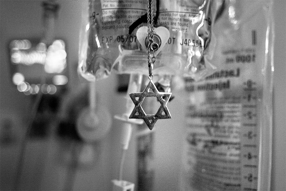 Pepa hangs Mooda's necklace from the IV post in the hospital room. A Rabbi made regular visits to the family there.