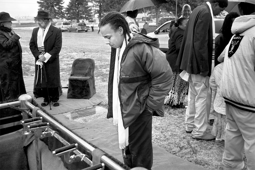 Abdul Robinson-Rashad, Mooda's nephew, pauses to look into her grave following her burial in Albuquerque. Abdul and Mooda, who were close in age, grew up together.