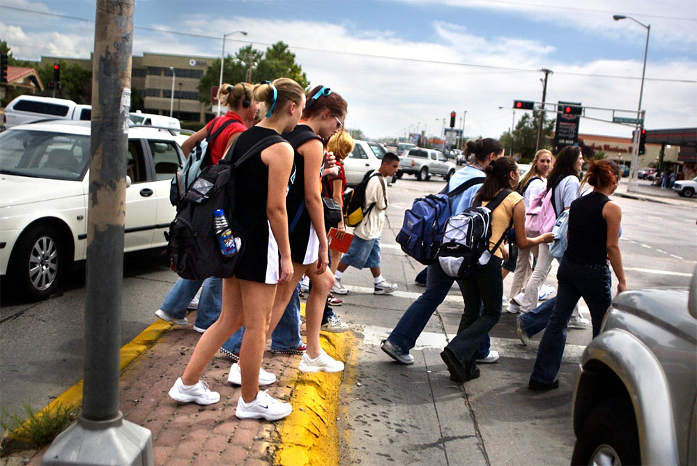 Following school at Albuquerque's Del Norte High School, students stand in the median waiting for a break in traffic so they can cross to the safety of the sidewalk. The intersection San Mateo and Montgomery Boulevard is one of the busiest and most deadly the city.