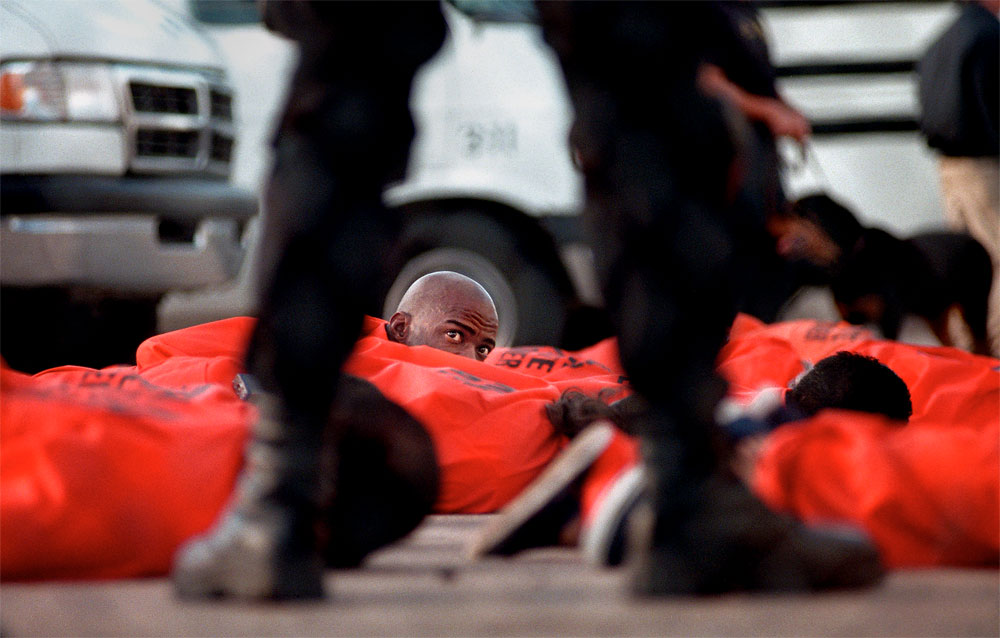Inmates from the Guadalupe County Correctional Facility in Santa Rosa, N.M., lie on the ground after filing out of buses and vans near dawn at Kirtland Air Force Base in Albuquerque. Guards searched them one by one before they boarded a plane bound for Wallens Ridge State Prison in Virginia. New Mexico Gov. Gary Johnson made the decision to send the inmates out of state after violence at the Santa Rosa prison resulted in the death of a guard.