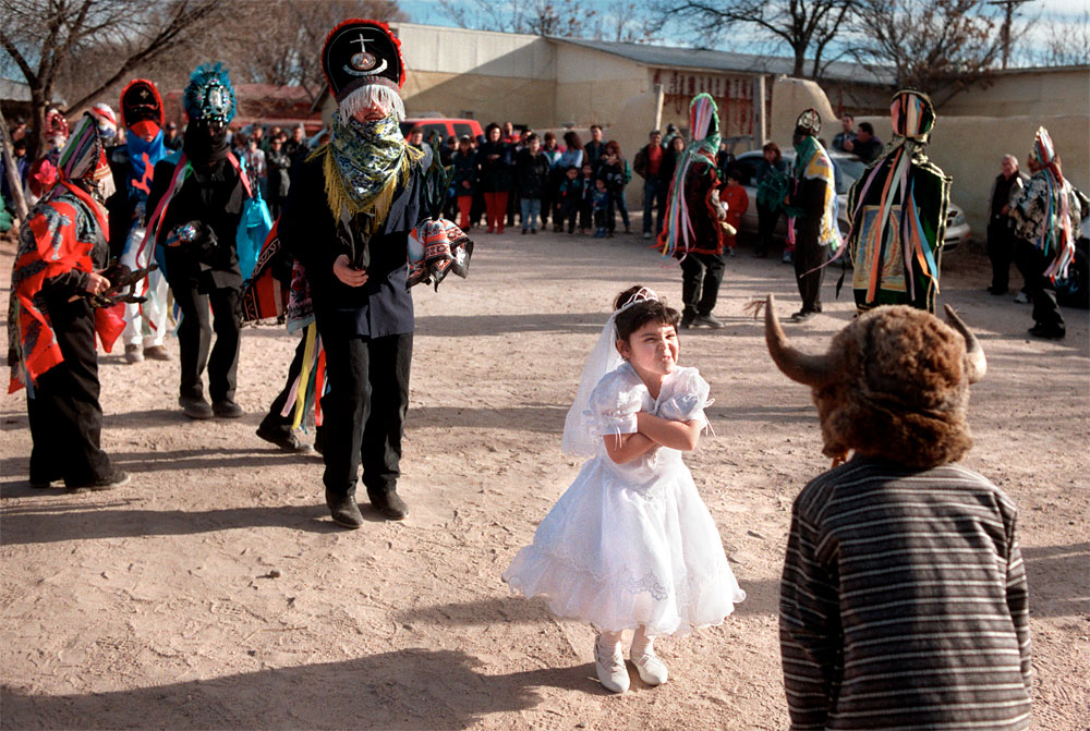 During a Matachine dance performed in Alcalde, N.M., Alexandra Salazar, 5, playing the role of Malinche, makes an unrehearsed sneer at El Torito, {quote}the little bull{quote} who represents evil to Salazar's good. The dance is traditional throughout the Rio Grande Valley.
