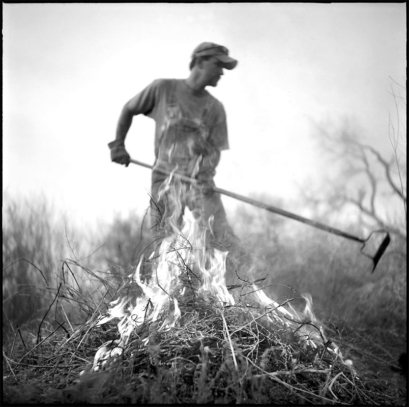 Chris Tyler performs his annual chore of removing and burning dry brush from a stretch of the Santa Ana Acequia that runs along his property in Algodones, N.M.