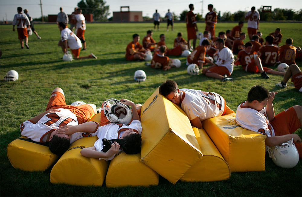 After narrowly completing a series of drills, members of Eldorado High School's football team collapse onto pads along the sideline. During the second day of practice and the first day of school classes. Charlie Dotson, Eldorado's new coach, quickly returned them to the practice field following a brief water break.