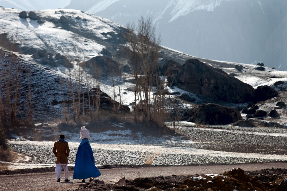 Images © Graham Crouch 2013 A local Hazara man and his wife walk down the highway leading out of Bamiyan home to the empty Buddhas of Bamiyan niches, two 6th century monumental statues of standing buddha carved into the side of a cliff in the Bamyan valley in the Hazarajat region of central Afghanistan.The valley is home to many Hazara's, who have often made up vast numbers of refugees to Australia, having been persecuted and driven from their homes in both Afghanistan as well as from Quetta in Pakistan where a lot of displaced Hazara fled to during the Taliban years. Bamiyan is home to a lot of Hazara who are Shia muslim and as such are looked down upon by the Sunni Pashto tribes that make up the population majority in Afghanistan.